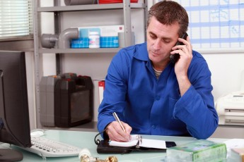 Plumber taking a call in an office and making an appointment in